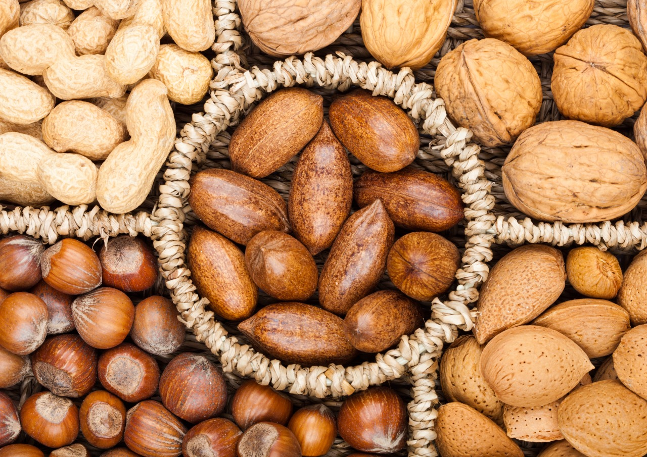 Basket reach in various kinds of nuts in shells, pecans, almonds, hazelnuts, peanuts and walnuts