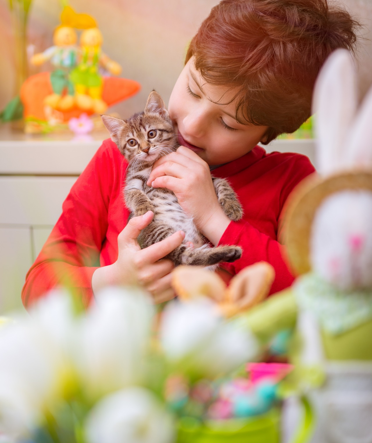 Child playing with small cat