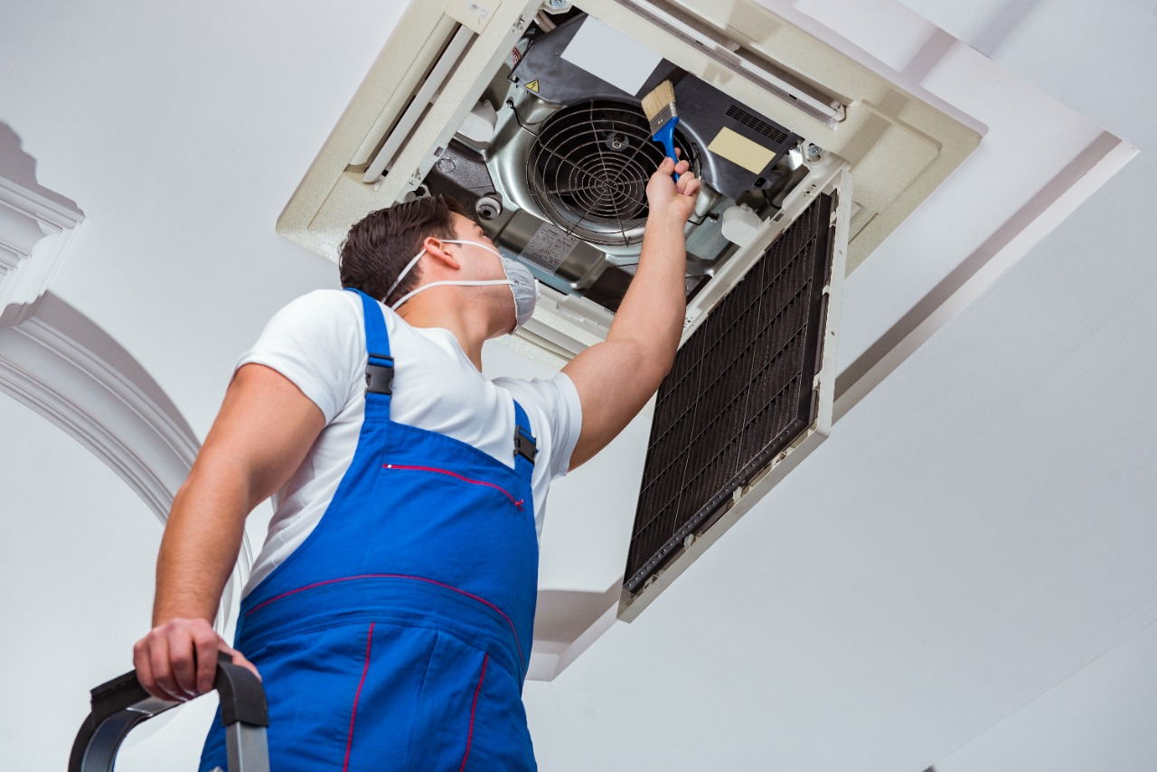 Man cleaning dander off air conditioning unit filter