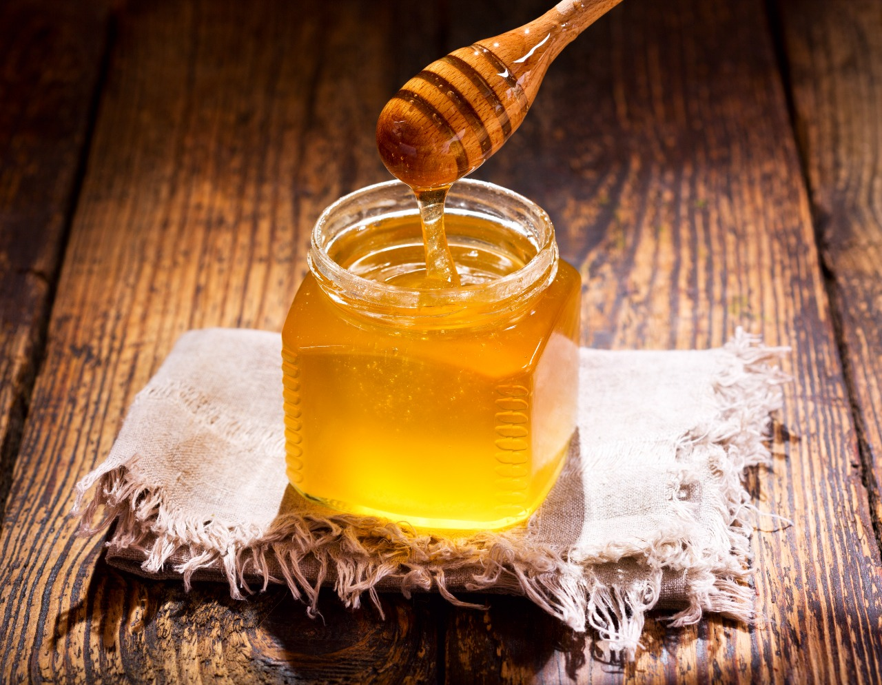 honey in a jar on a wooden table